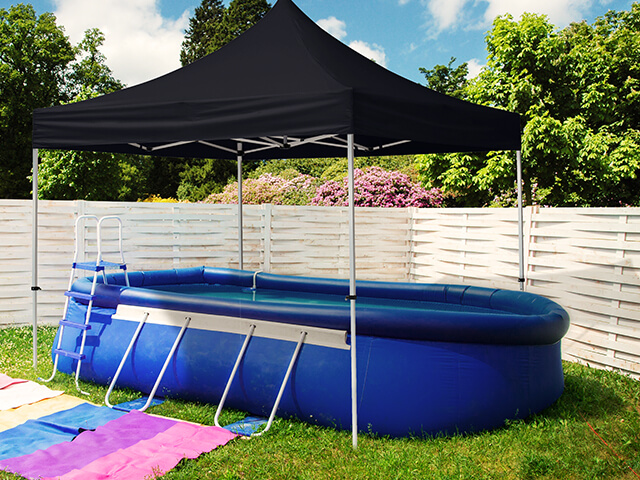 A pop up gazebo providing shade over an inflatable pool
